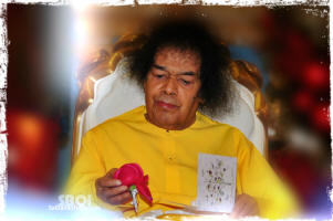 sri-sathya-sai-baba-holding-a-rose-in-his-hand-wearing-yellow-robe.